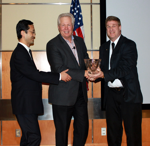 Dr. Warner C. Greene (center) receives Career Award crystal from Center for Retrovirus Research Director Dr. Patrick L. Green (right) and Center member Dr. Li Wu (left)